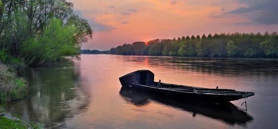 La douceur angevine : un bateau sur la Loire au couché du soleil.